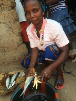 Village woman prepares fish and chicken legs
