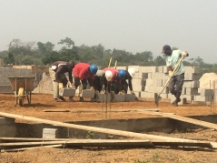 Workers use cement blocks in unison to compact foundation soil